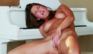 Seductress on a piano bench plays with her juicy pussy
