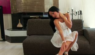 Black haired beauty in a white dress seduces by stripping