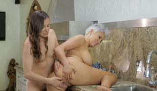 Mature housewife fucks a cute young lesbian in her kitchen